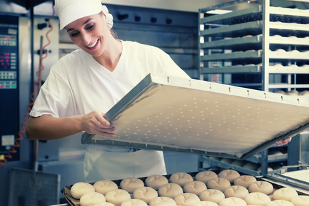 Baker woman with sheet of bread in bakery baking in oven, filtered image photo