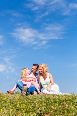 centred: Parents and daughter sitting on grass, total view, centred, centered Stock Photo