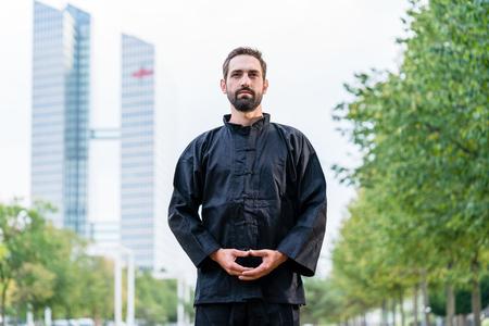 man meditating: Man meditating doing martial arts in city