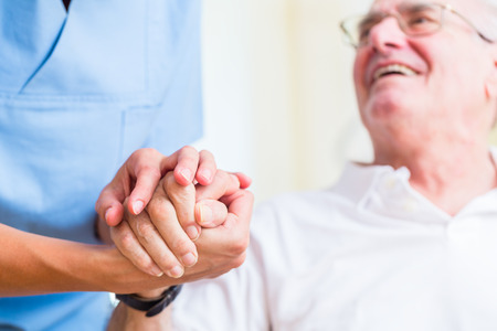old hand: Nurse holding hand of senior man in rest home
