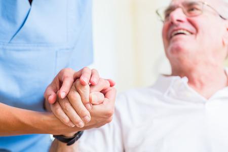 Verpleegster die de hand van de hogere mens in rusthuis