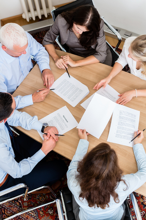 co workers: Lawyers having team meeting in law firm reading documents and negotiating agreements