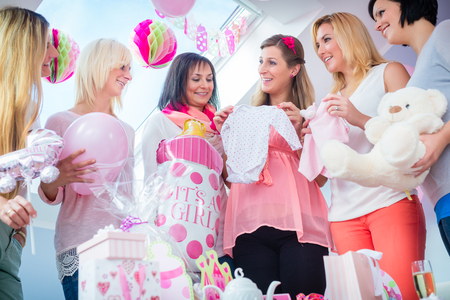 Expecting Mother with presents on baby shower party getting a romper suit, her friends sitting on couch