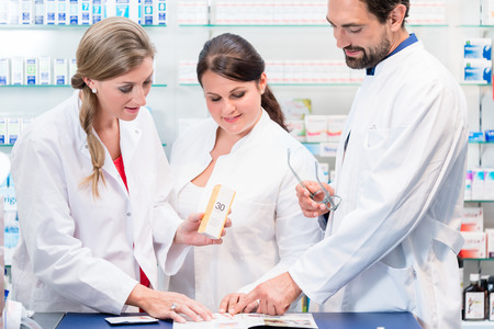 drug store: Team of pharmacists in drug store checking pharmaceuticals