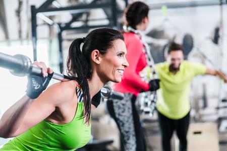Vrouw in functionele training tillen gewichten in gymnastiek Stockfoto