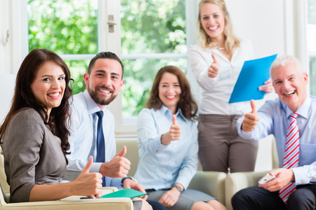 co workers: Business men and women in office having success showing thumbs up Stock Photo