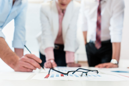 financial symbol: Business people analyzing financial data - glasses on graph, symbol for focus and detail Stock Photo