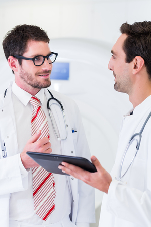 tomograph: Doctors discussing images of x-ray scan standing in front of CT machine in hospital Stock Photo