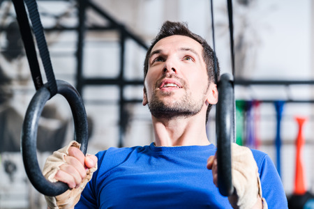 functional: Man at rings doing fitness exercise in gym