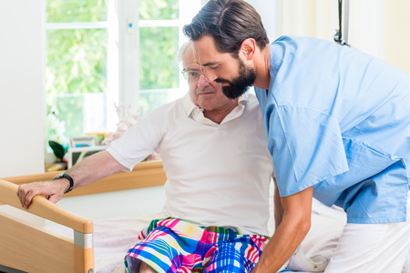 Elderly care nurse helping senior from wheel chair to bed