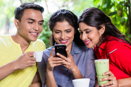 asian group: Indian girl showing pictures on smart phone to her friends in an Indian cafe
