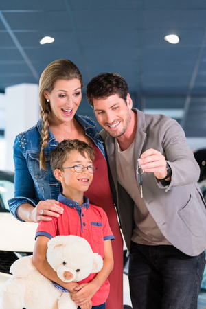 bought: Family showing key to newly bought car in showroom of auto dealership