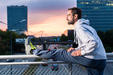 gymnastics: Runner stretching in front of office building at sunset