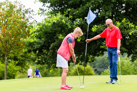 woman golf: Senior woman and man playing golf putting on green
