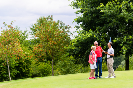 woman golf: Golf pro with senior woman and man analyzing results Stock Photo
