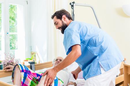 Altenpflege Krankenschwester hilft Senior Mann vom Rollstuhl ins Bett Standard-Bild - 56931249