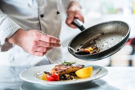 그의 식당 부엌에서 음식을 마무리하는 요리사