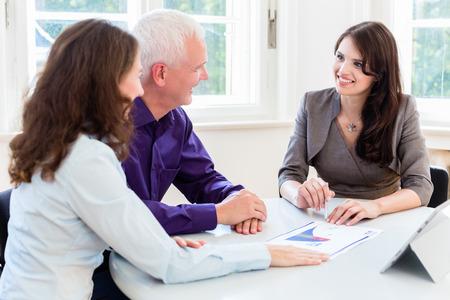 impuestos: Superior de la mujer y el hombre en la planificación financiera de jubilación con el consultor o asesor