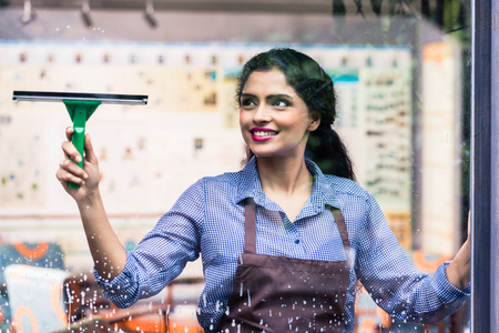 Indian employee cleaning windows with squeegee Stock Photo - 59916478