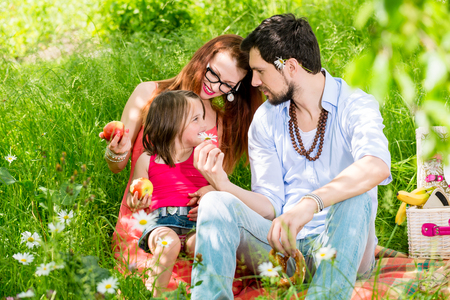 young wife: Family eating in summer meadow sitting on grass having a picnic