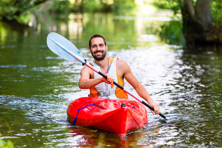 creek: man driving with kayak on forest river Stock Photo