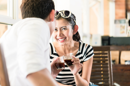 korean man: Asian couple, Indonesian woman and Korean man, in cafe flirting while drinking coffee, barista in the background Stock Photo