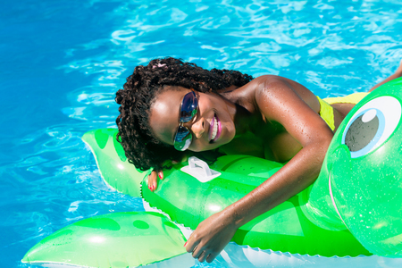 summer heat: Girls in swimming pool water with inflatable anmimal
