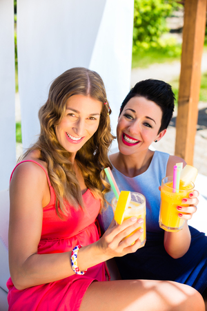 lake beach: Two friends at lake beach with drinks relaxing Stock Photo