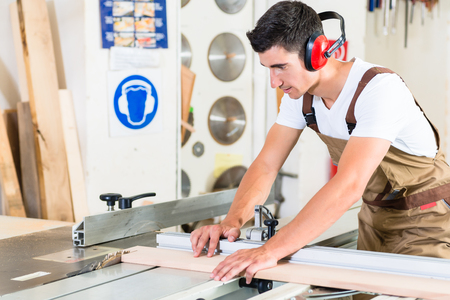 cabinet maker: Carpenter cutting wooden plank in his workshop