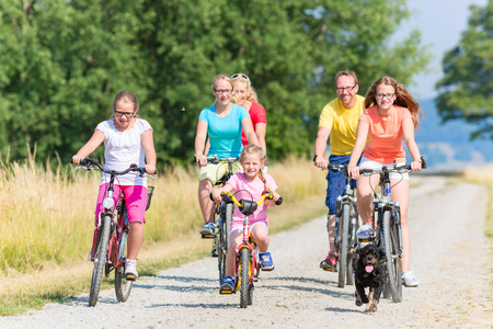 group of men: Family on bikes riding down dirt path, mother, father and children together