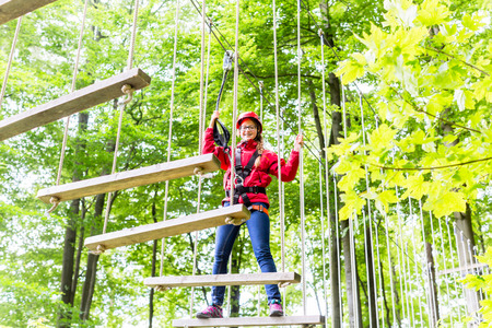courses: Teenage girl, walking on rope bridge in climbing course enjoying the trill of the sport Stock Photo