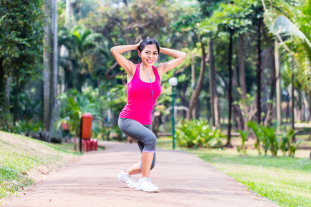 women sport: Asian Woman stretching in fitness exercise or sport training in tropical park Stock Photo