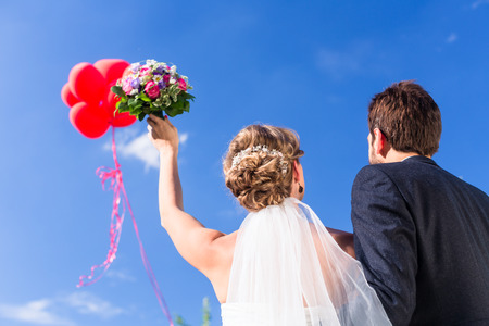 balloon bouquet: Bride and groom at wedding with helium balloons Stock Photo