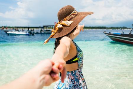 Vrouw wilde haar man om haar te volgen in de vakantie of huwelijksreis naar het strand door de oceaan Stockfoto