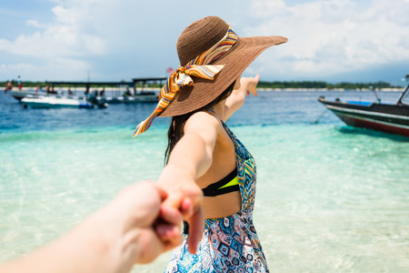 wanting: Woman wanting her man to follow her in vacation or honeymoon to beach by the ocean Stock Photo