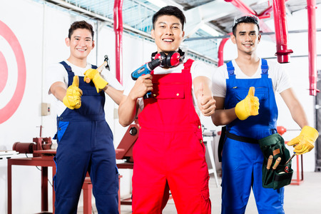 cabinet maker: Three Asian industrial workers, a manufacturing team, standing proud in factory giving the thumbs up sign