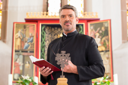Priest in church with bible in front of altar