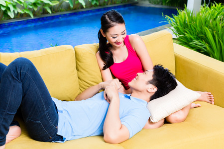 huddling: Asian couple huddling on sofa in living room of home or house, a swimming pool in the background Stock Photo
