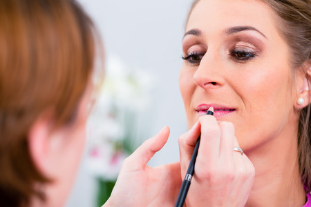 beauty parlor: Beautician applying lip color on woman in beauty parlor