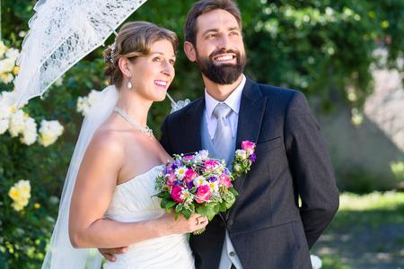 rose garden: Bridal couple embracing each other in summer garden