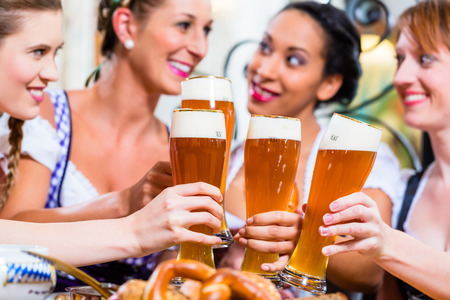 tracht: Girls toasting with wheat beer in Bavarian pub in front of pretzel