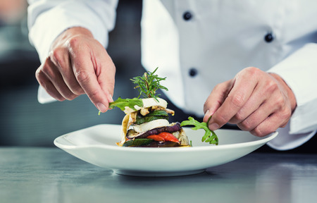 Chef in Restaurant garnishing vegetable dish, crop on hands, filtered image