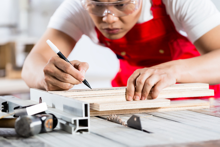 cabinet maker: Asian Chinese Carpenter cutting wood with circular saw in his workshop