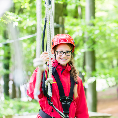 clambering: Girl roping up in high rope course exercising the necessary safety precautions