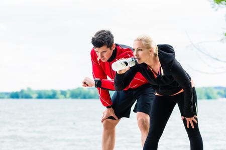 fitness hombres: Mujer y hombre en descanso de correr en frente del lago Foto de archivo