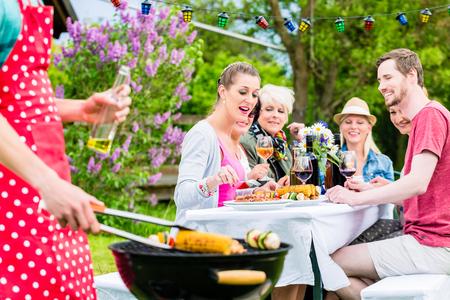 L'uomo grigliate di carne e verdure su festa in giardino, i suoi amici a mangiare la carne barbecue