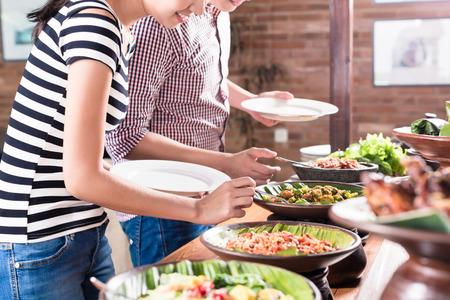 Mujer asiática y hombre de elegir los alimentos en el buffet de Indonesia en el restaurante