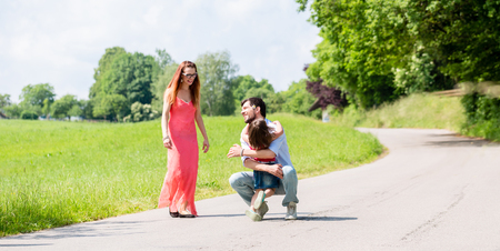 mom dad: Mamá, papá y la hija que tiene caminata en la ruta en verano