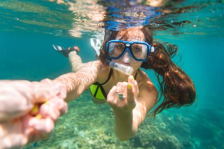 snorkelling: Snorkelling woman in yellow bikini makes tempting gesture in ocean