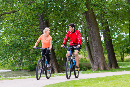 outdoor fitness: Woman and man on mountain bike in the woods